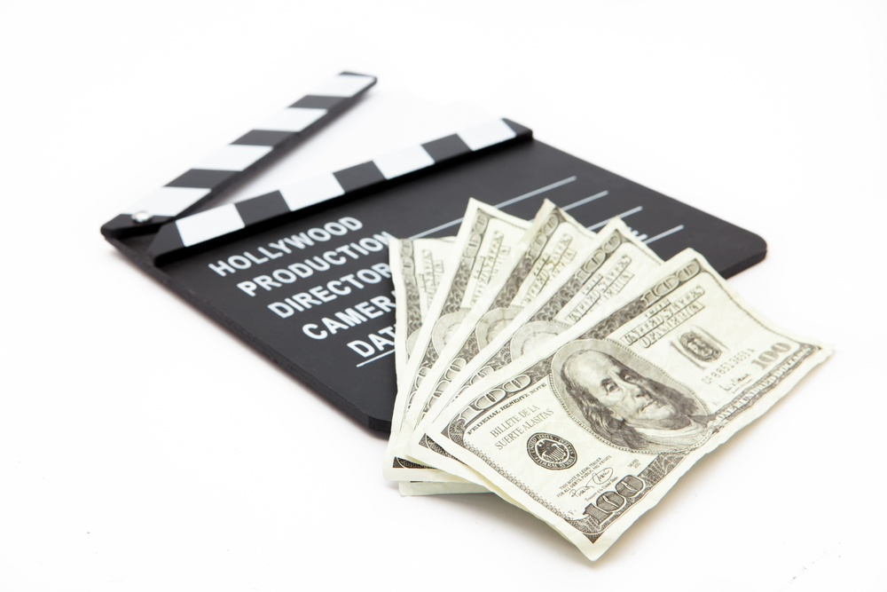 Film slate and money lying against white background.jpeg